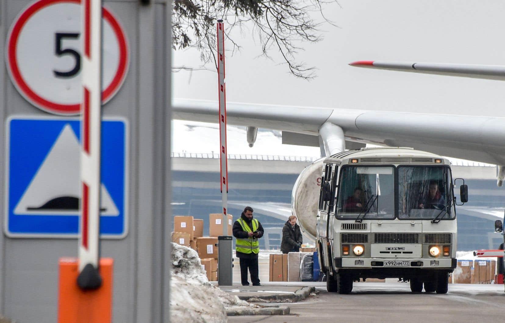 Un bus sort de l'aéroport Vnukovo II de Moscou alors que l'avion qui a ramené 46 diplomates russes et les membres de leur famille est vu sur la piste d'atterrissage, samedi.