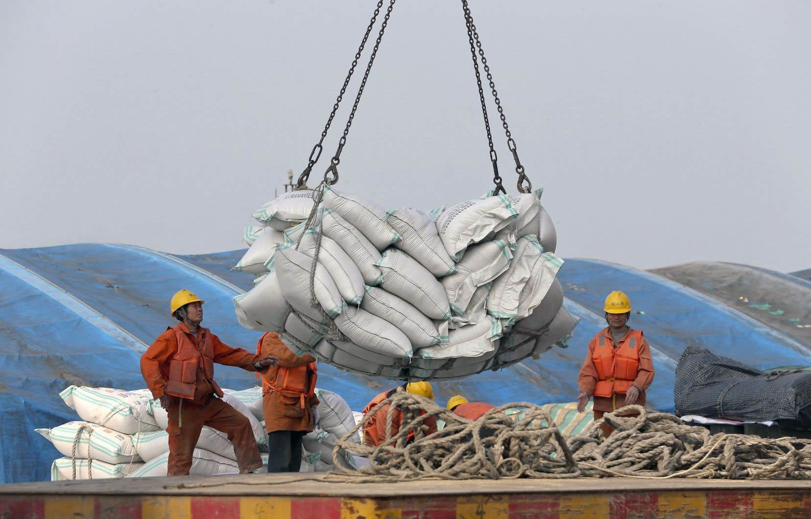 Des travailleurs chargent des fèves de soya au port de Nantong, en Chine.