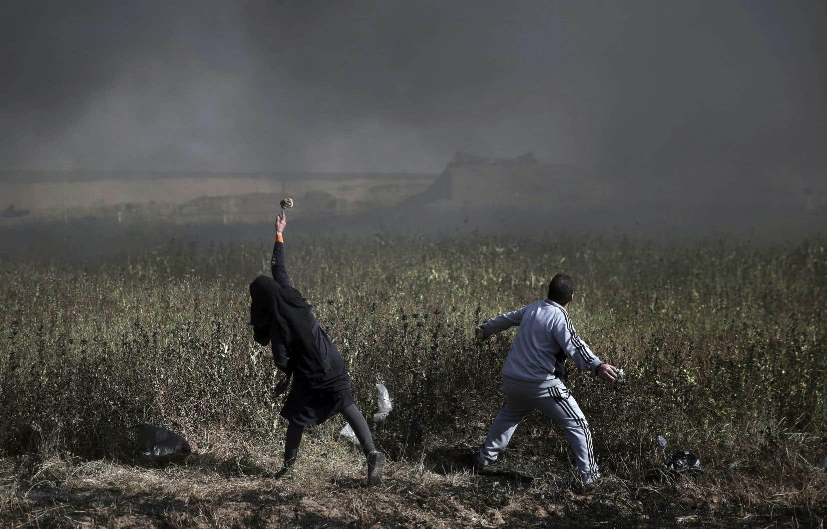 Des Palestiniens lancent des pierres vers les troupes israéliennes à la frontière gazaouie vendredi.