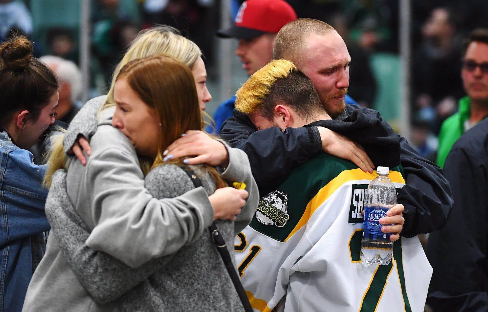 Des gens endeuillés se réconfortent en assistant à une veillée à l'aréna Elgar Petersen, domicile des Broncos de Humboldt, en l'honneur des victimes de l'accident d'autobus à Humboldt.