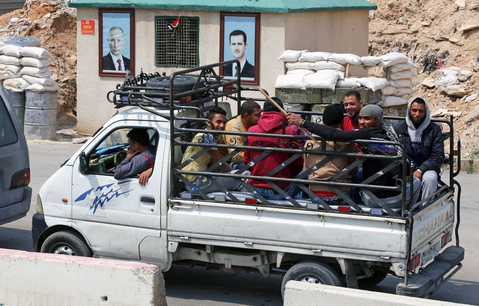 Des combattants du groupe Jaich al-Islam et leurs familles quittant Douma, jeudi