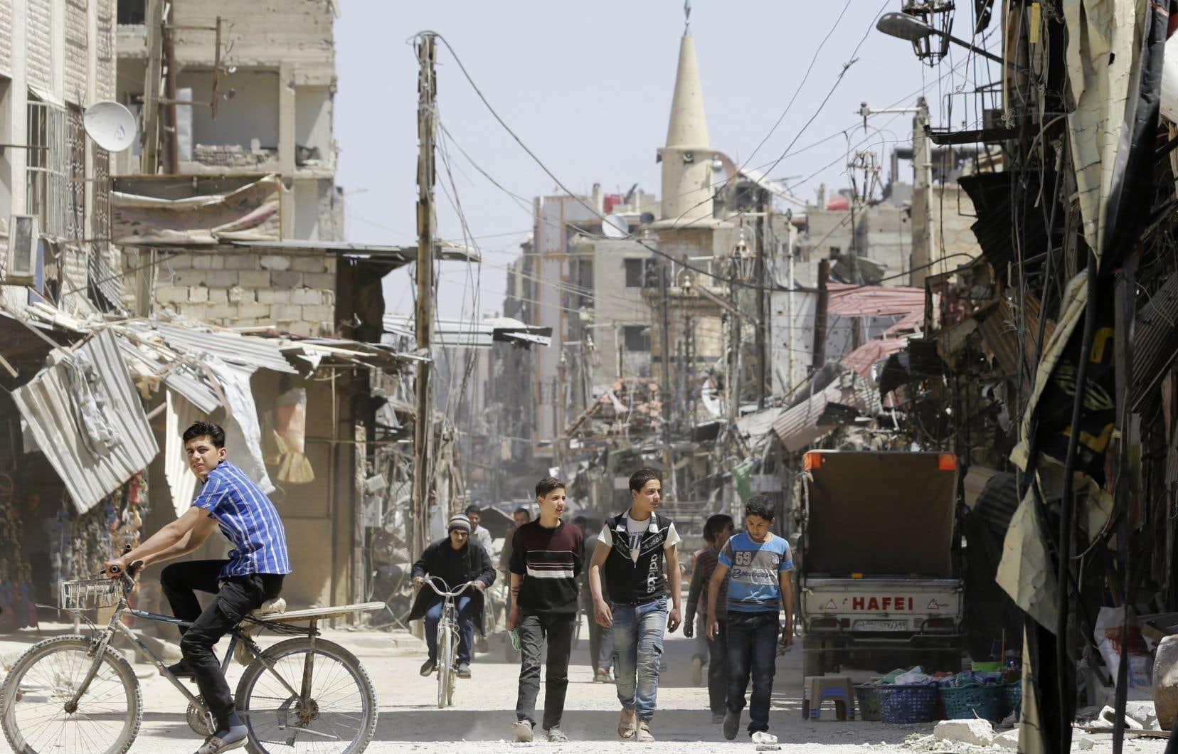 Des Syriens dans les rues de Douma, récemment reprise aux rebelles par les forces syriennes.