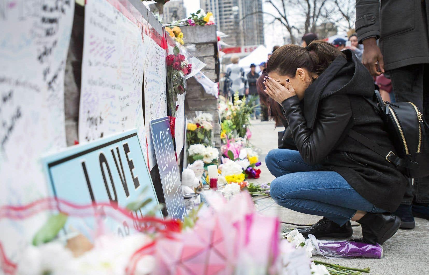 Une femme se recueille près de l'endroit qui a été le théâtre de l'attaque au camion-bélier, lundi.