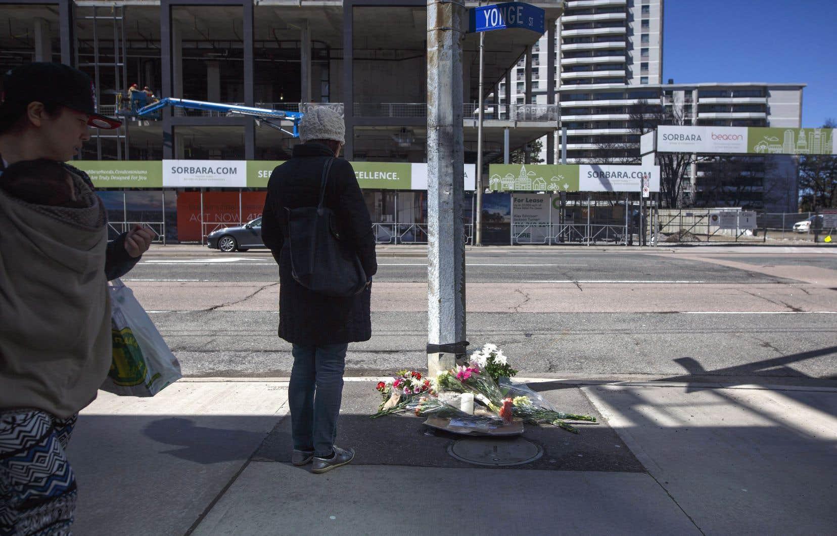 Une femme se tient devant un lieu de recueillement spontané dressé pour les victimes de l'attaque de Toronto sur la rue Yonge.