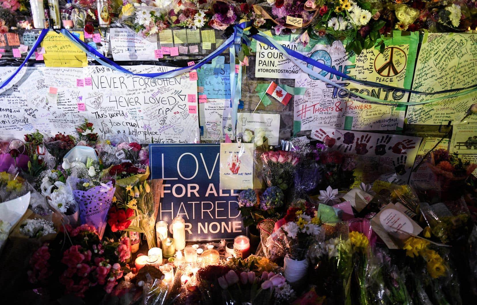Des fleurs, des messages et des bougies sont disposés lors d'une veillée sur la rue Yonge à Toronto, mardi dernier.