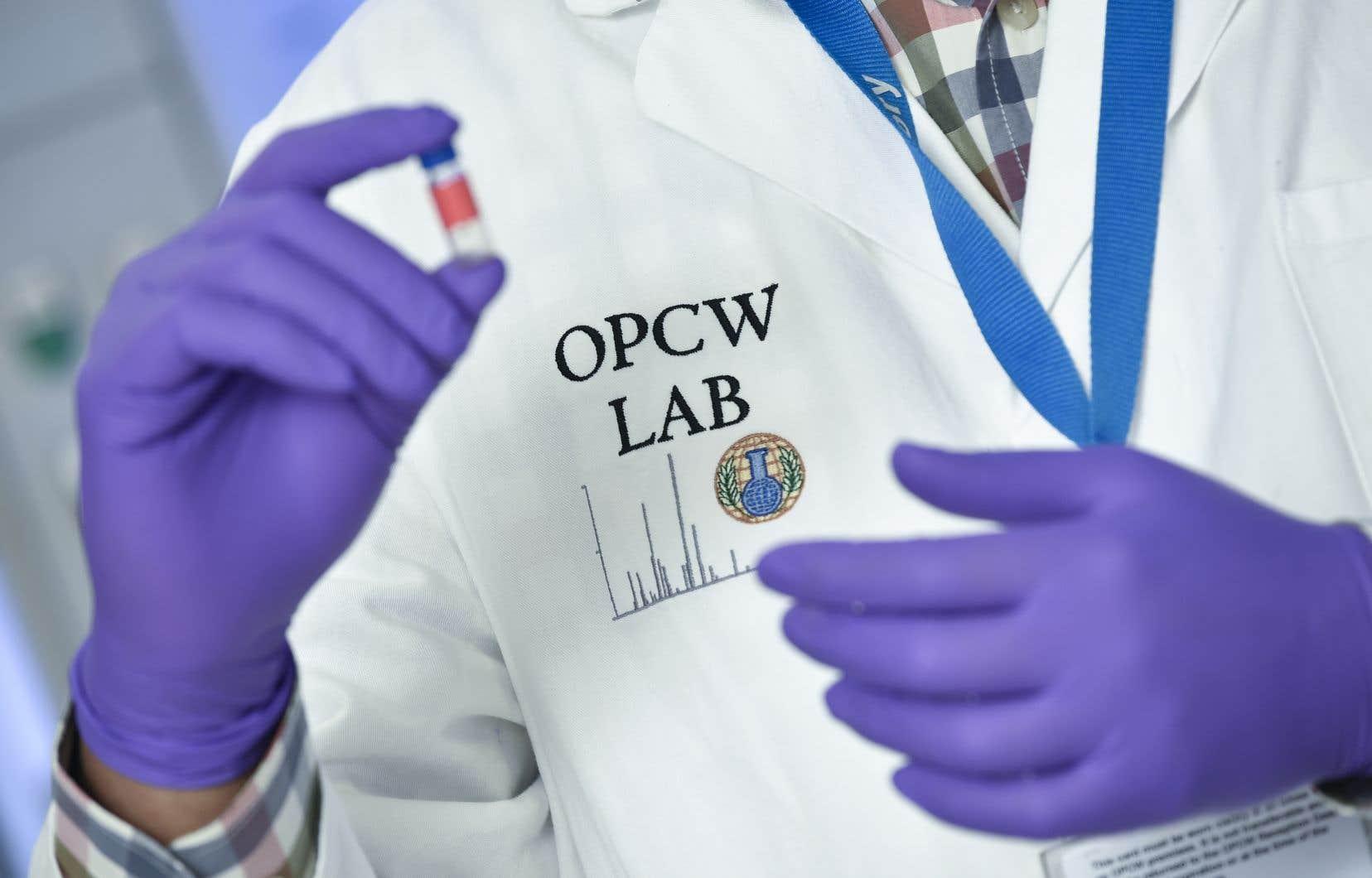 Un technicien de laboratoire contrôle un flacon d'essai au siège de l'OIAC, à La Haye, aux Pays-Bas.