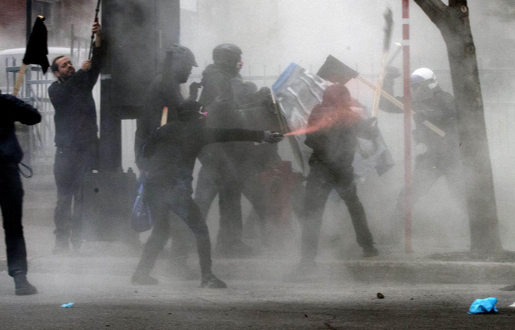 Un affrontement entre des protestataires cagoulés et des policiers a divisé le groupe de manifestants à peine cinq minutes après le début du rassemblement.