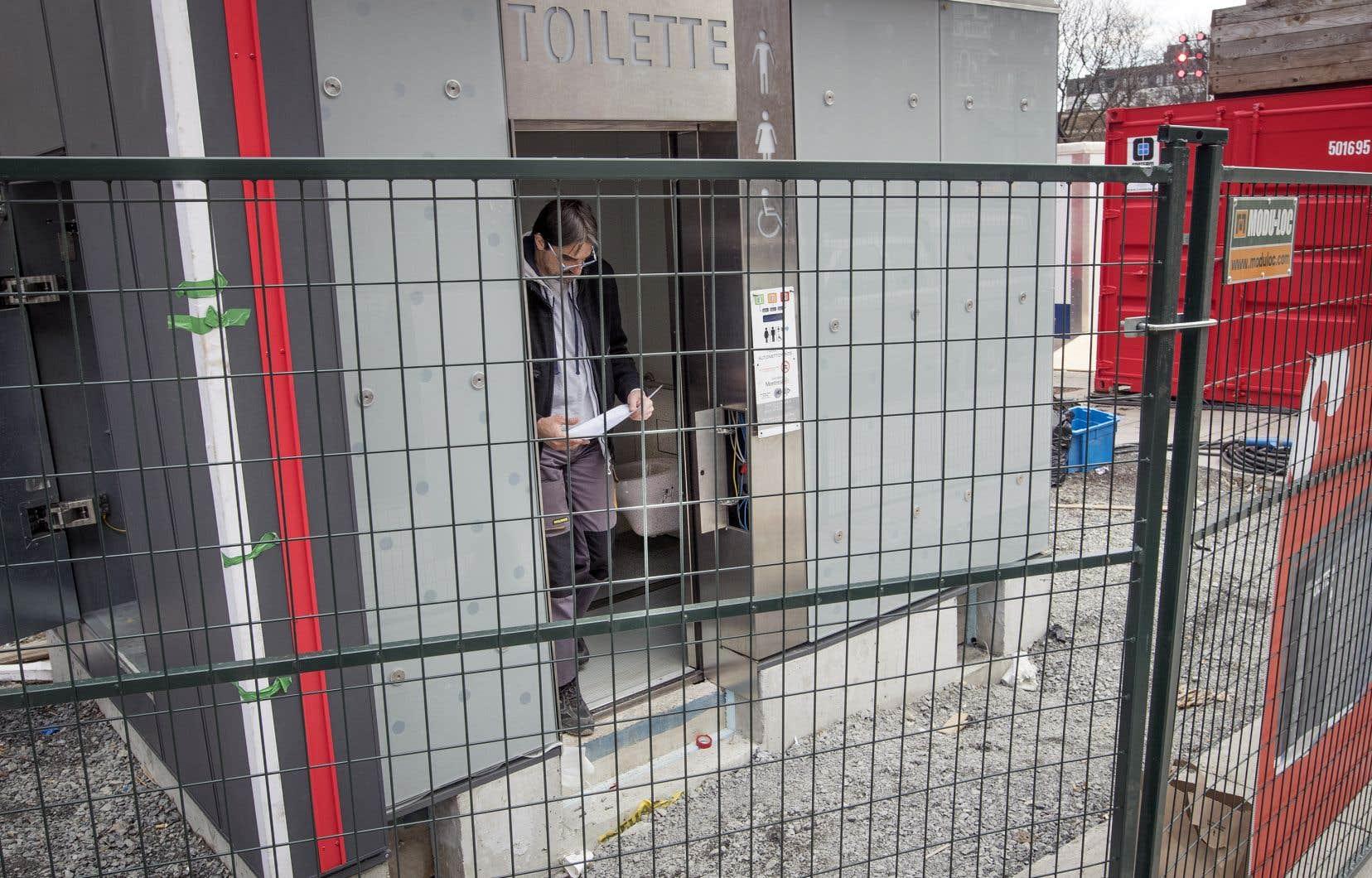 Une toilette autonettoyante en cours d'installation, sur la place Émilie-Gamelin