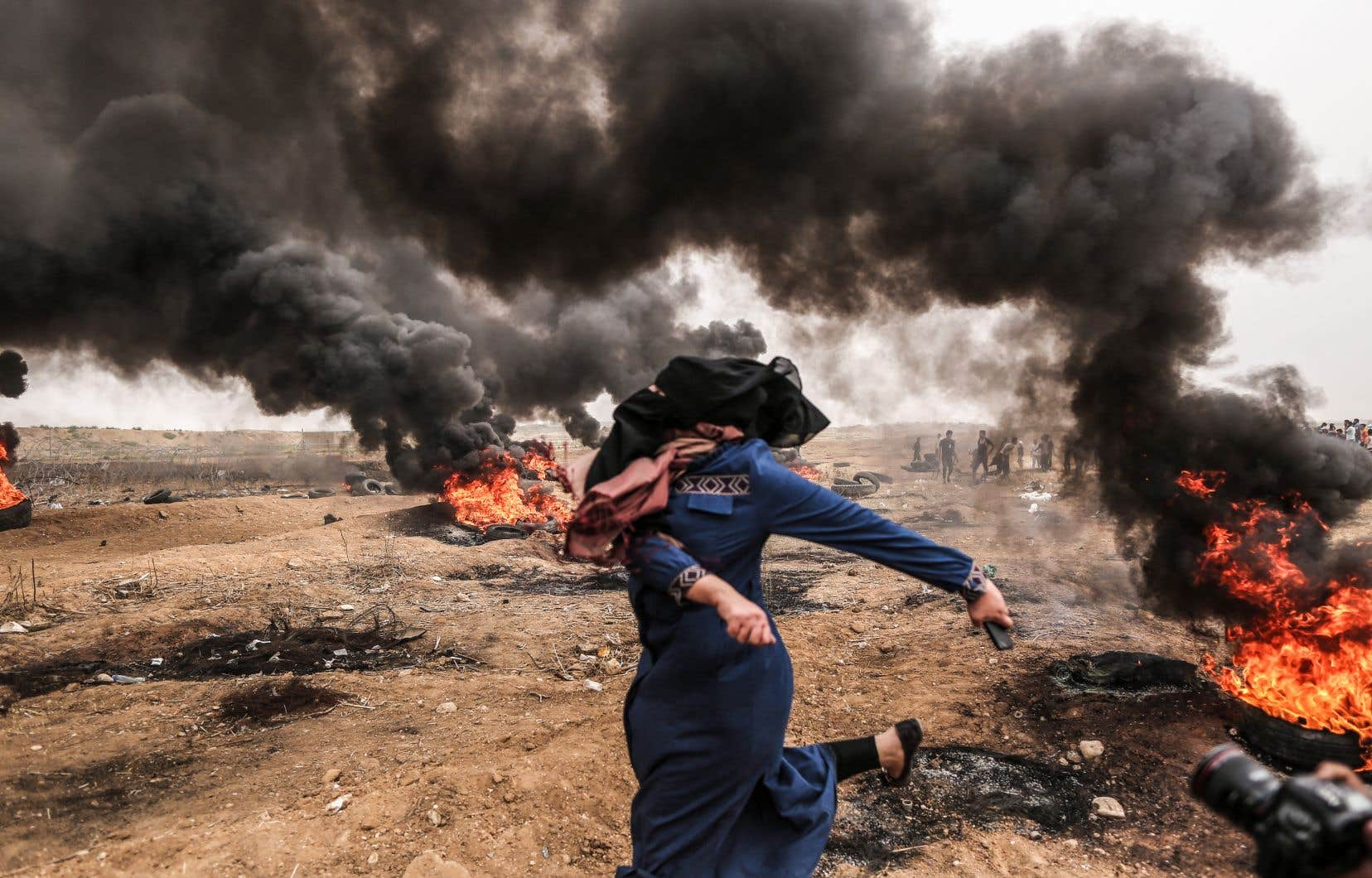 Une femme palestinienne a lancé des pierres en direction des soldats israéliens lors de heurts à la frontière entre Gaza et Israël, vendredi.