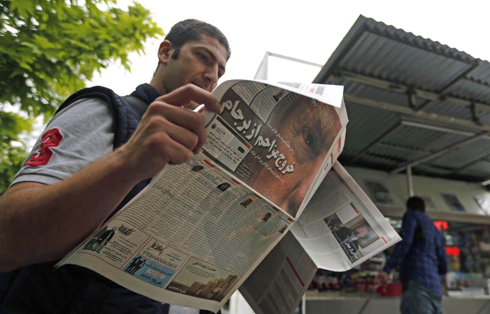 Un Iranien consulte un journal qui relate le discours du président Trump, mercredi à Téhéran.