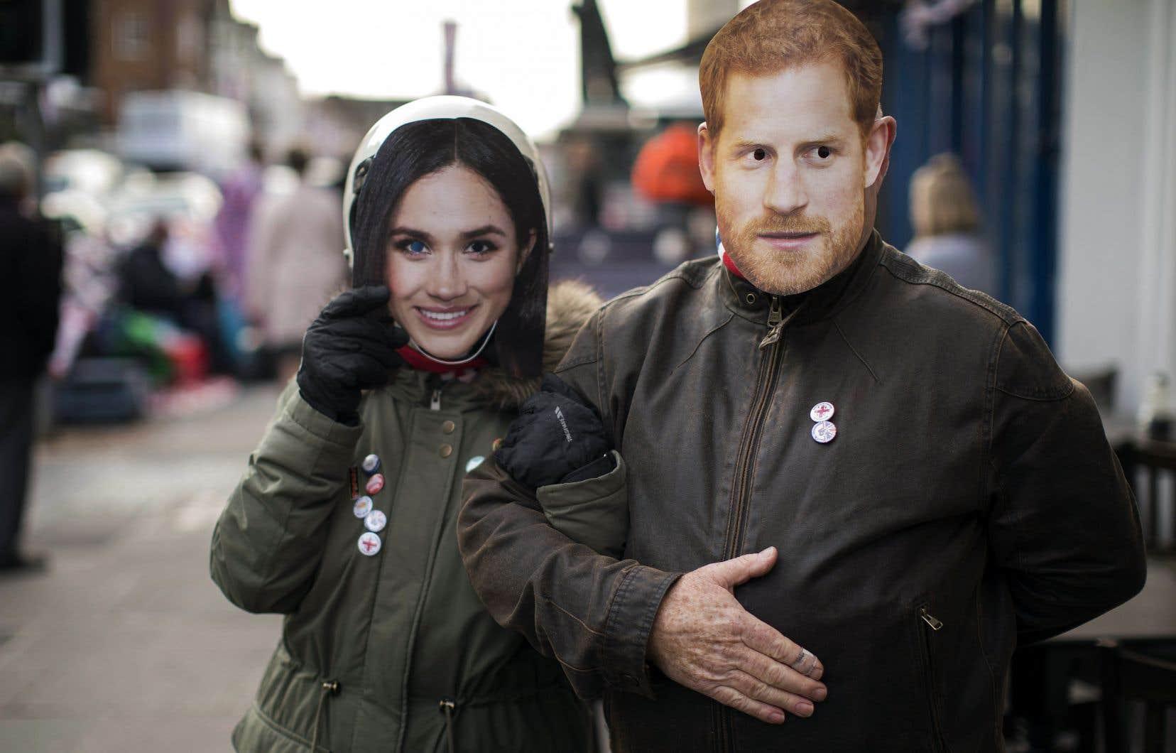 Un couple déambule dans Windsor affublé de masques à l'effigie des futurs mariés, à quelques jours du mariage royal prévu samedi en la chapelle Saint-Georges du château de Windsor.
