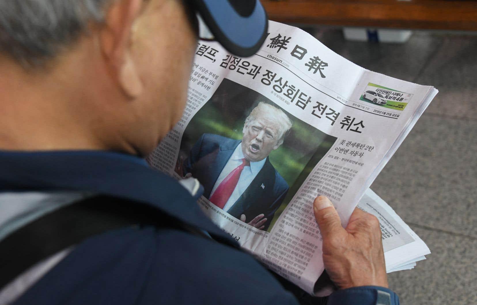 En Corée du Sud, un homme lit la manchette du journal au sujet de l'annulation de la rencontre qui se voulait historique.