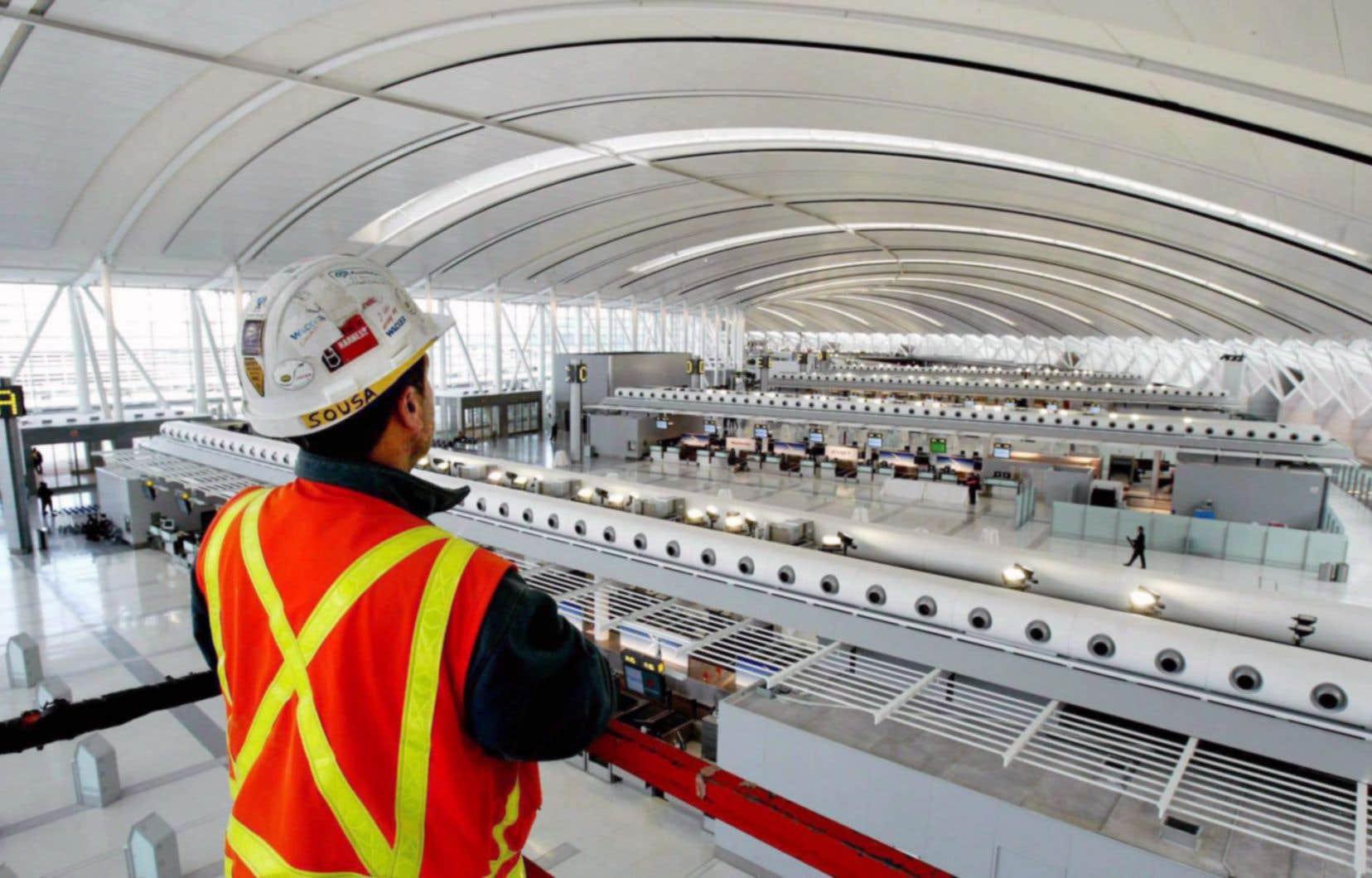 Un employé d'AECON surplombe, du haut de son élévateur à ciseaux, l'aéroport Pearson, à Toronto.