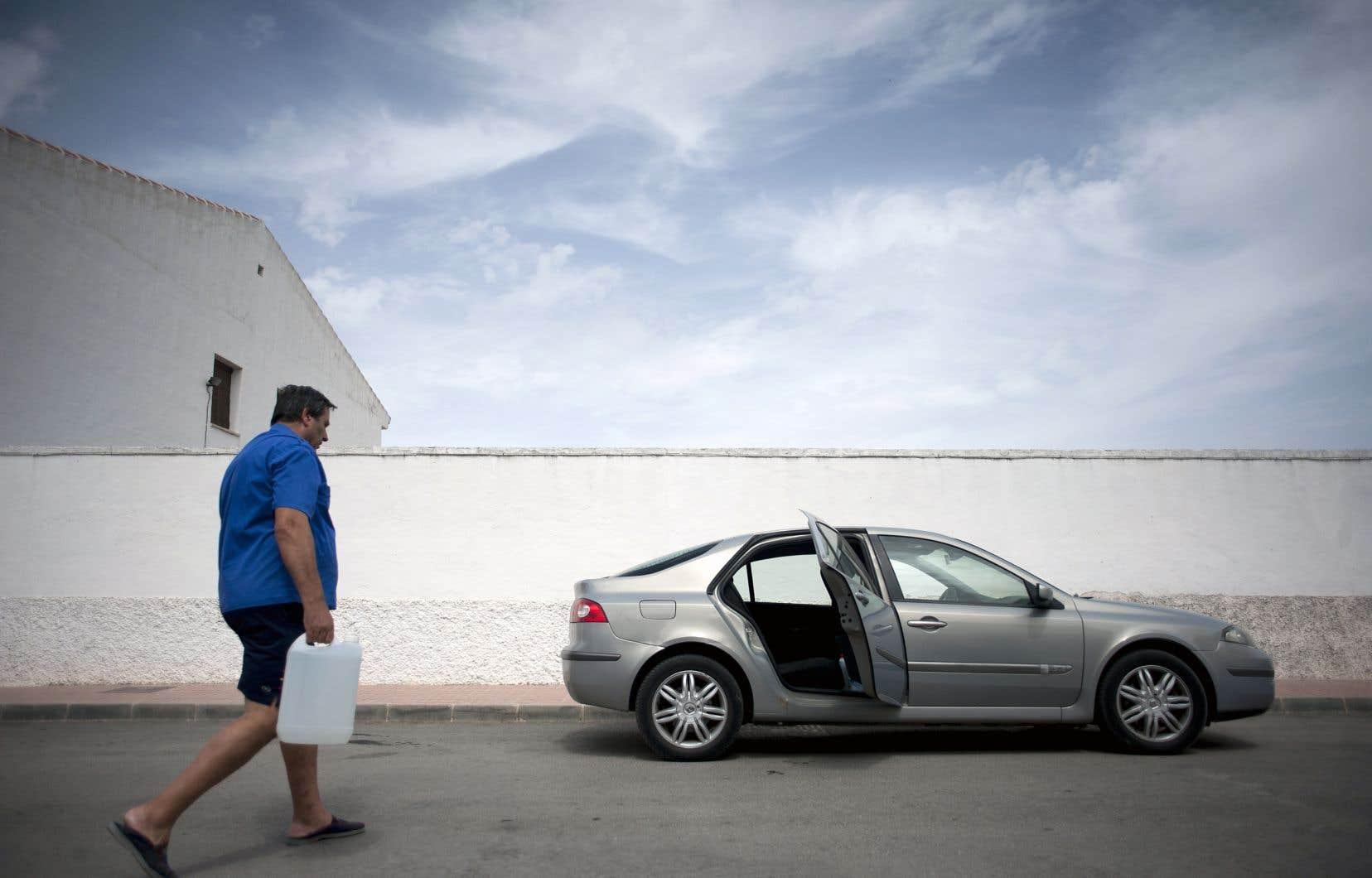 Un homme faisant provision d'eau dans des bidons en plastique pendant une sécheresse à Fuerte de Piedra, en Espagne, en août 2017