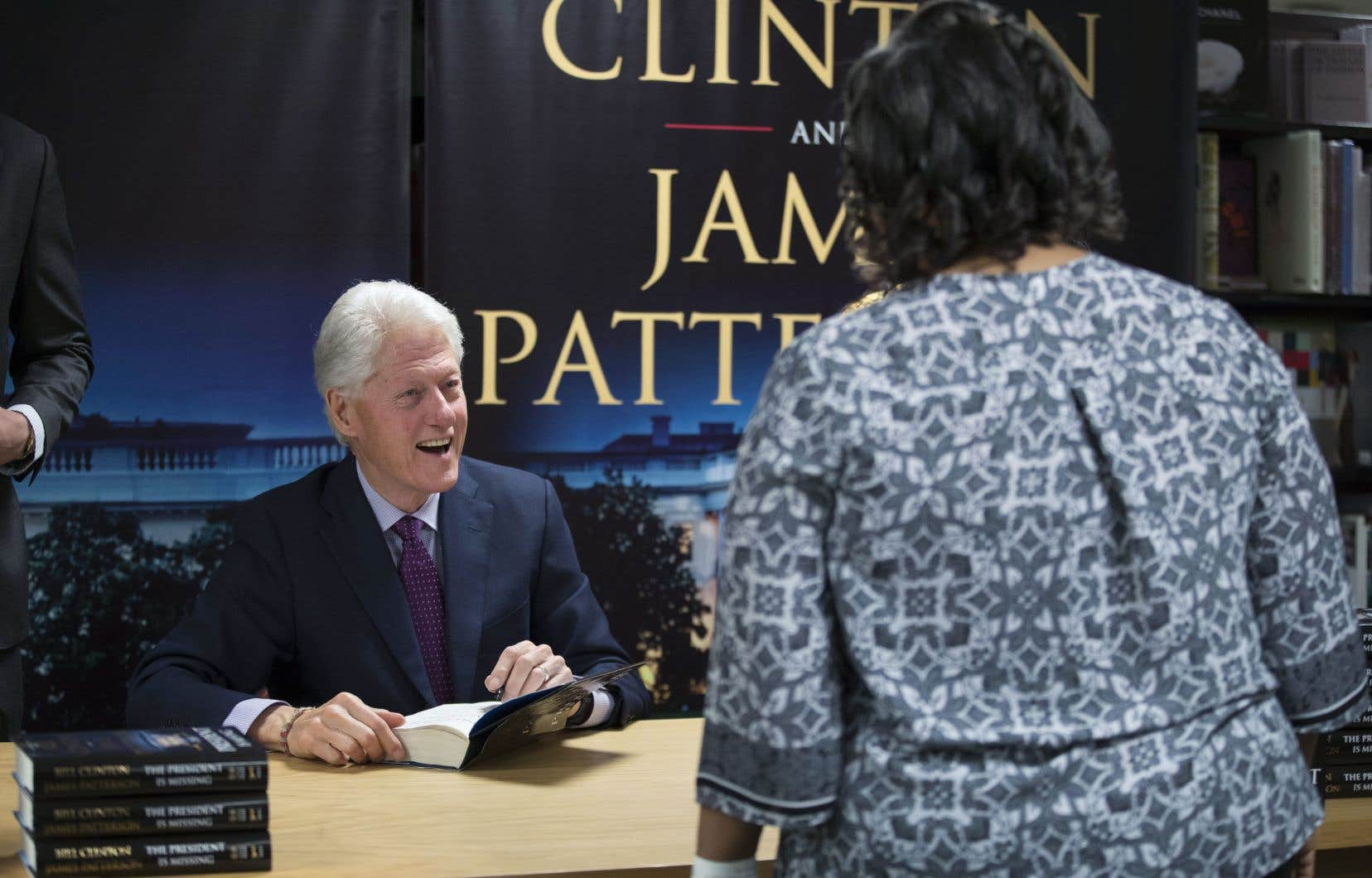 Bill Clinton autographiant le roman qu'il a écrit en collaboration avec James Patterson.