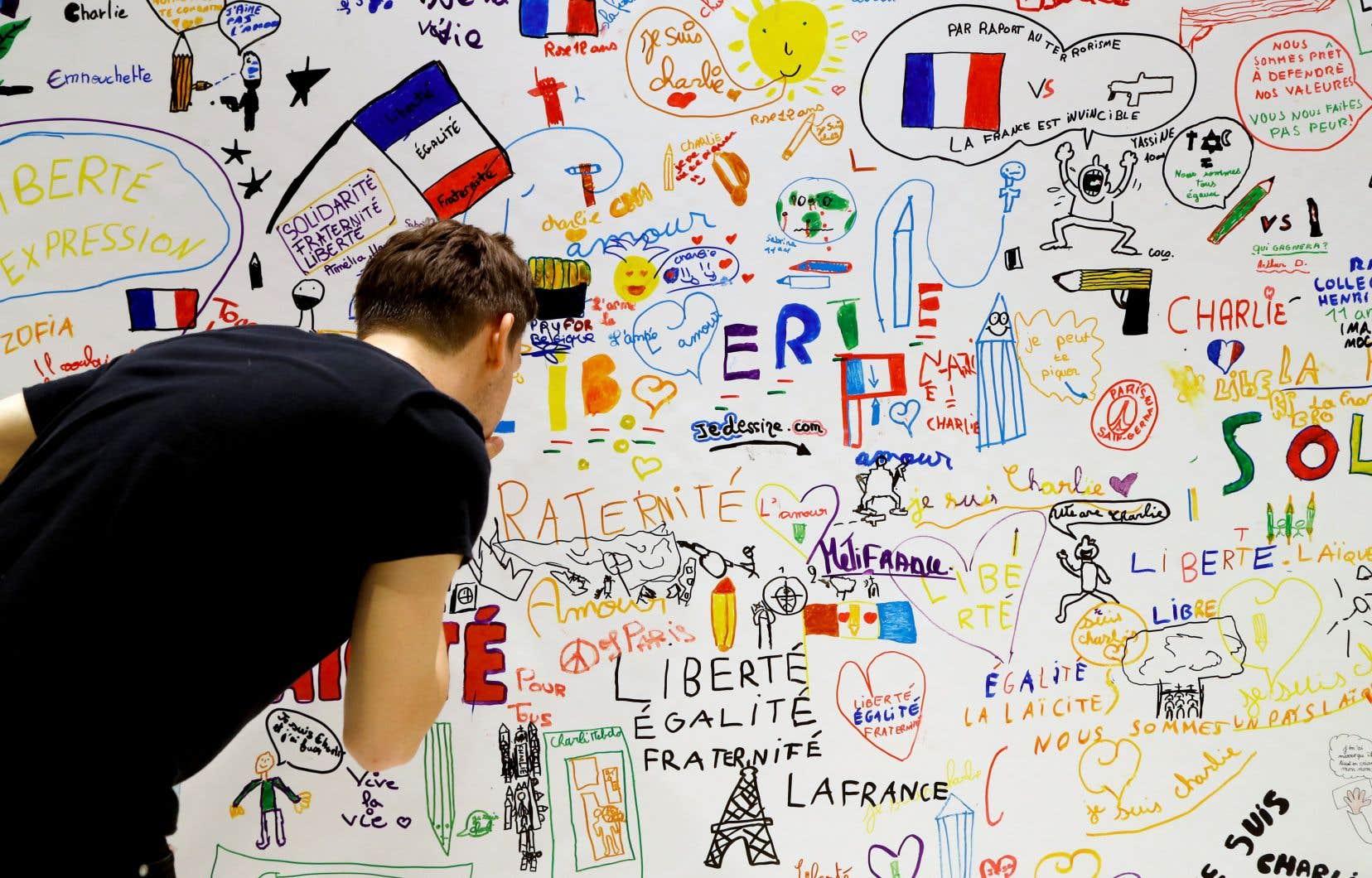 Un visiteur scrute une fresque dessinée par des enfants après l'attentat chez «Charlie Hebdo», exposée ces jours-ci à l'hôtel de ville de Paris.
