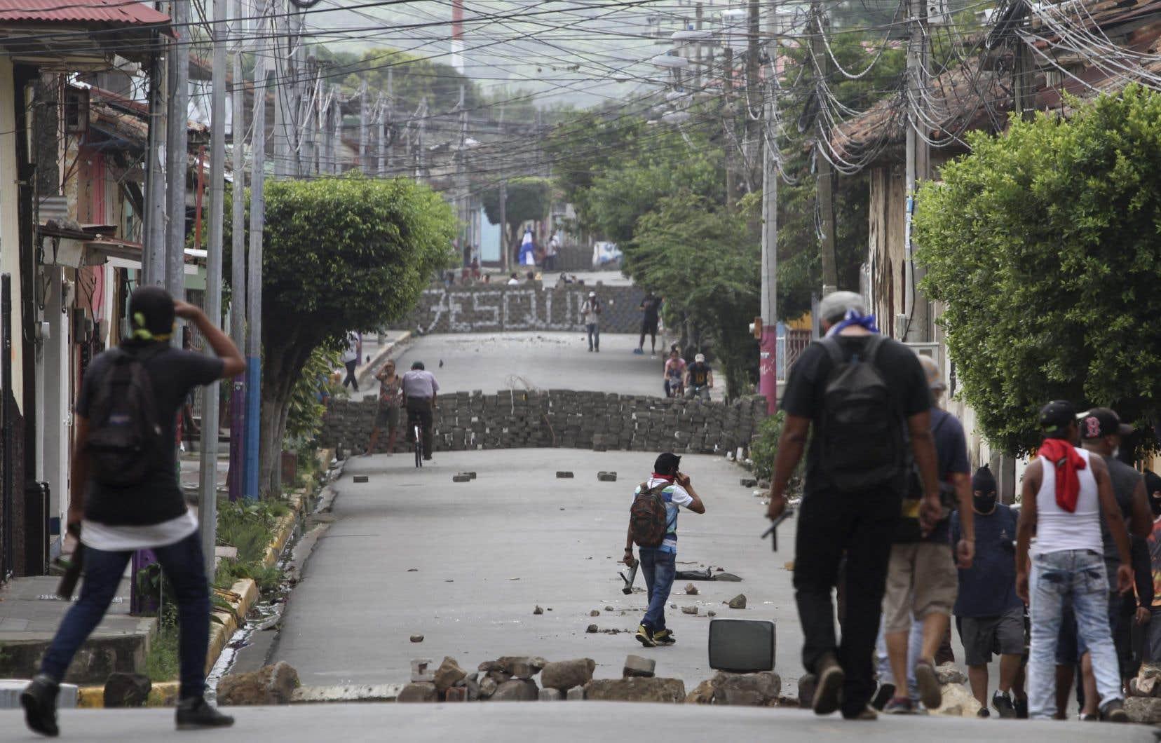 Des manifestants de l'opposition au gouvernement Ortega sont positionnés derrière des barricades, dans les rues de Masaya, samedi.