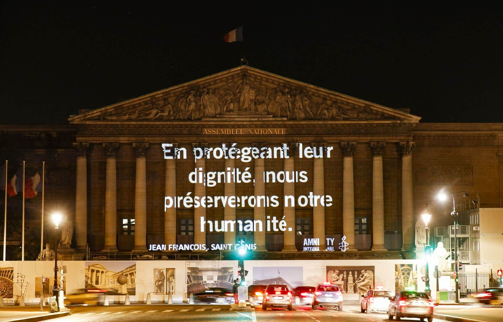 Dans la nuit, Amnesty International a projeté sur la façade de l'Assemblée nationale française des slogans en faveur de l'accueil des migrants.