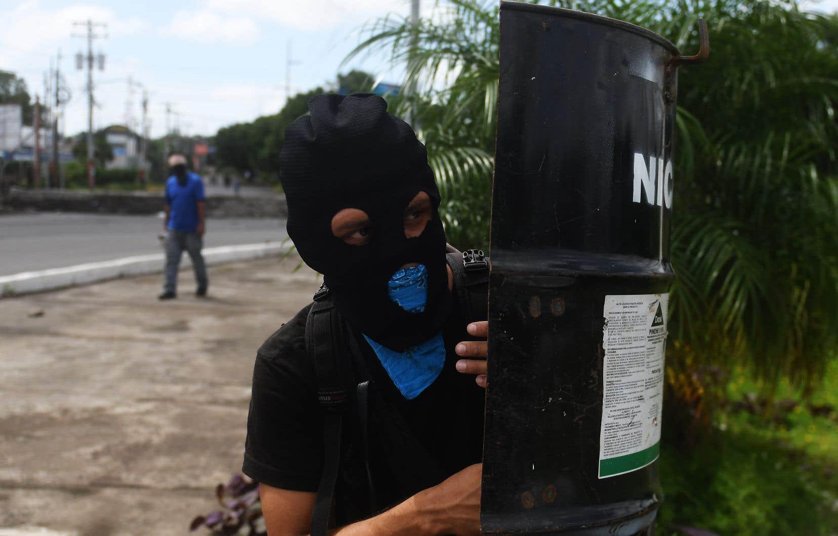 Un étudiant se protège avec un bouclier de fortune face aux attaques continues de la police anti-émeute et des membres de la Jeunesse Sandiniste, dans les environs de l'Université Nationale Autonome du Nicaragua, à Managua.