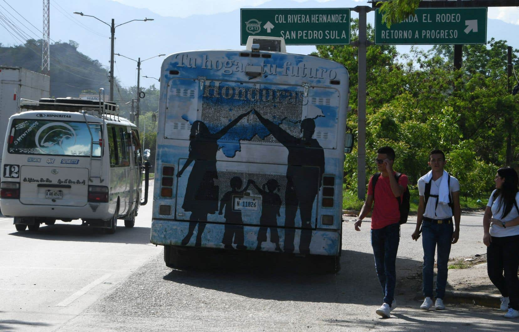 Trois jeunes immigrants honduriens sortent de l'aéroport de San Pedro Sula après avoir été expulsés des États-Unis, vendredi.