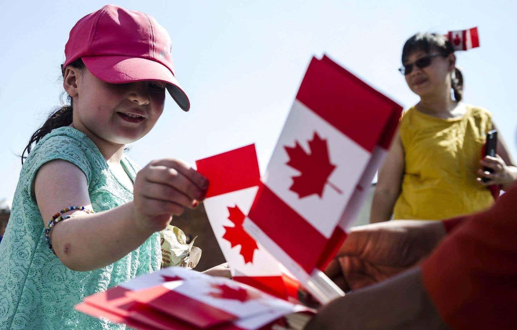 Zeyneb Gedik, 5 ans,prend un drapeau canadien lors de la parade organisée pour la Fête du Canada àScarborough, en Ontario.