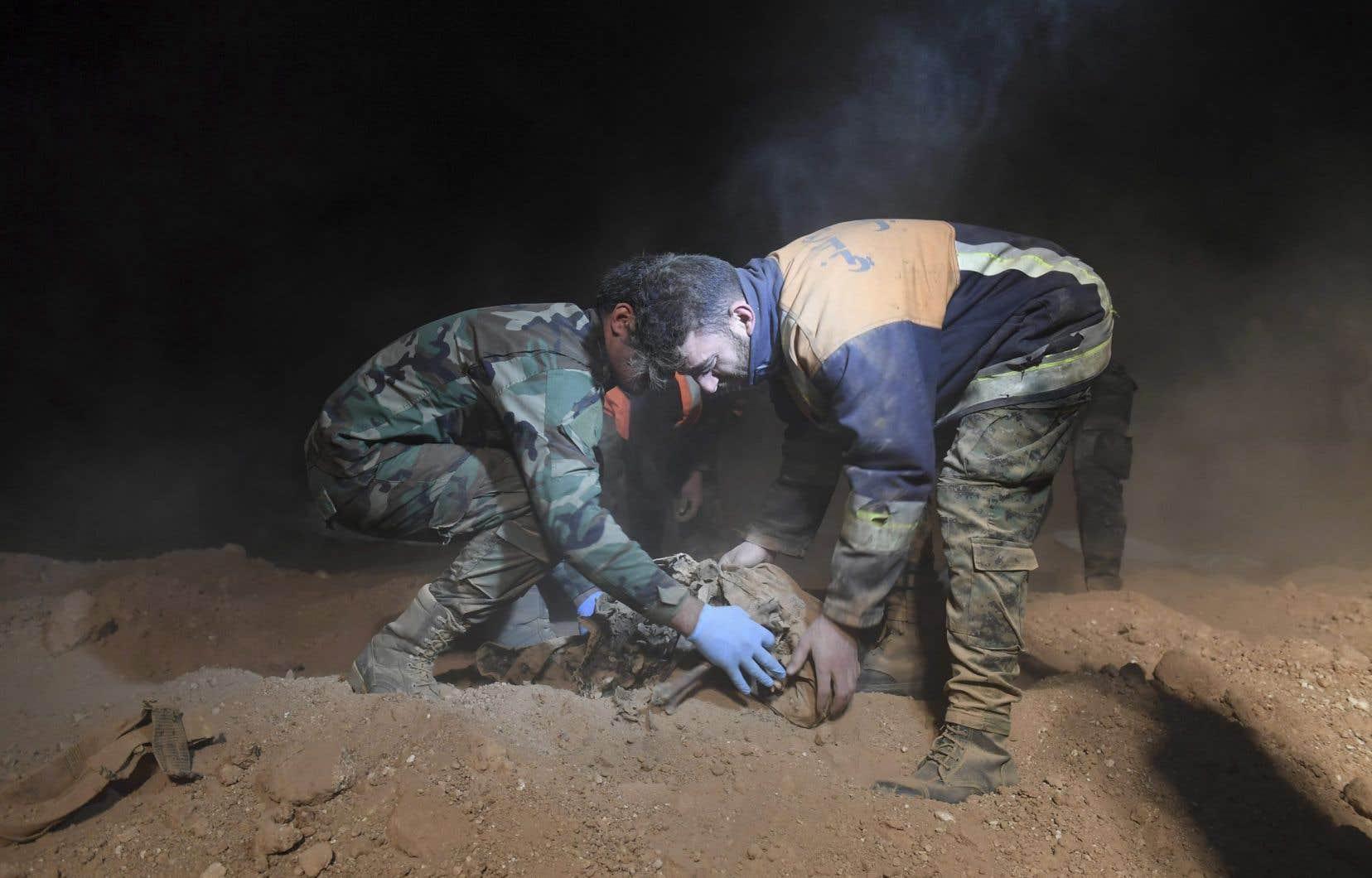 Des membres des forces de sécurité syriennes exhument des restes humains sur un site où deux fosses communes contiendraient les corps de civils et de soldats tués par les militants du groupe État islamique, dans le village de Wawi près de la ville de Raqqa, dans le nord du pays.