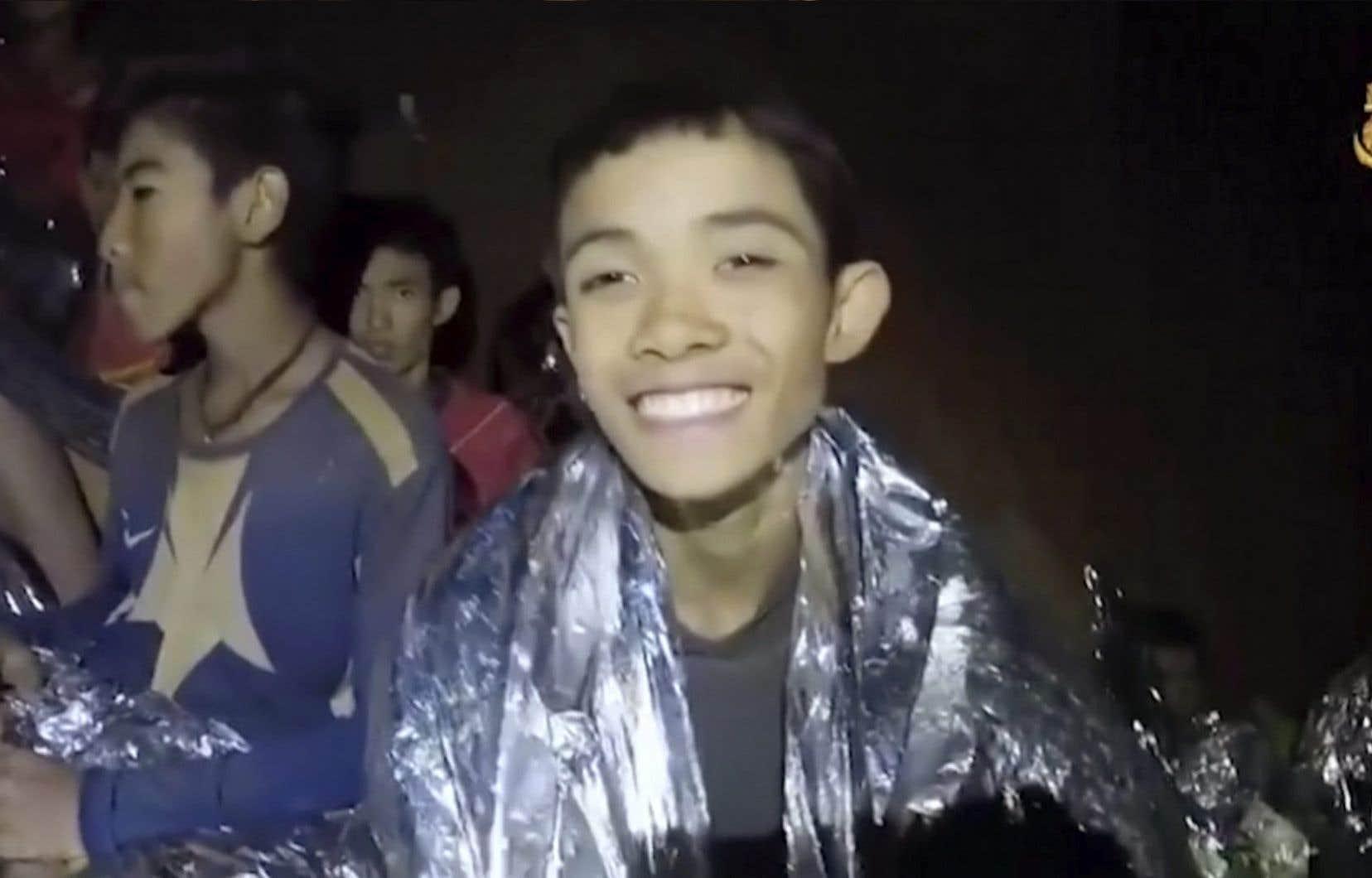 Les secouristes qui sont avec les enfants dans la grotte les remettent en forme et leur apprennent à se servir du matériel de plongée.