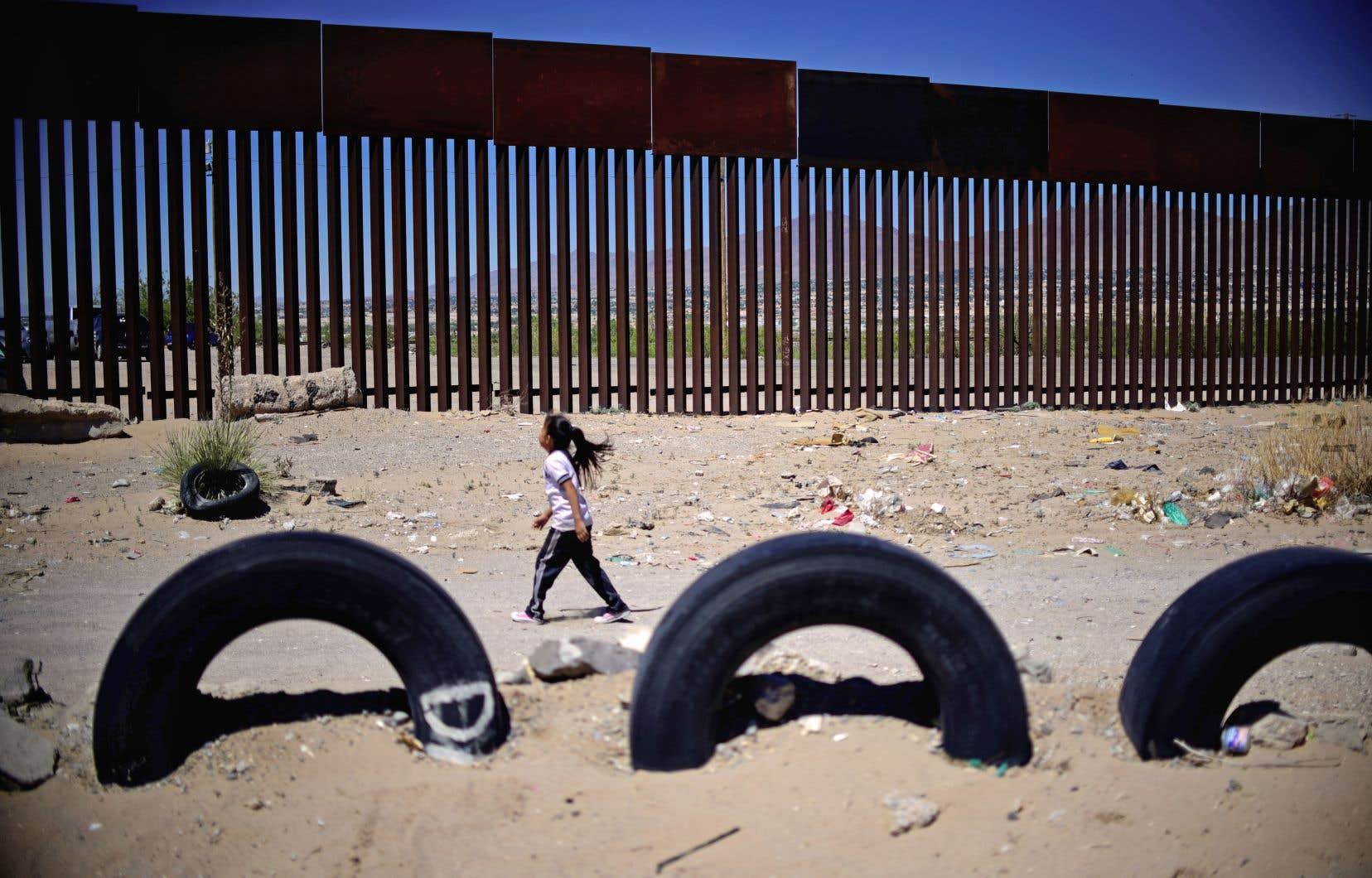 Une jeune fille longe la clôture métallique entre Ciudad Juárez, au Mexique, et Sunland Park (Nouveau-Mexique), aux États-Unis.