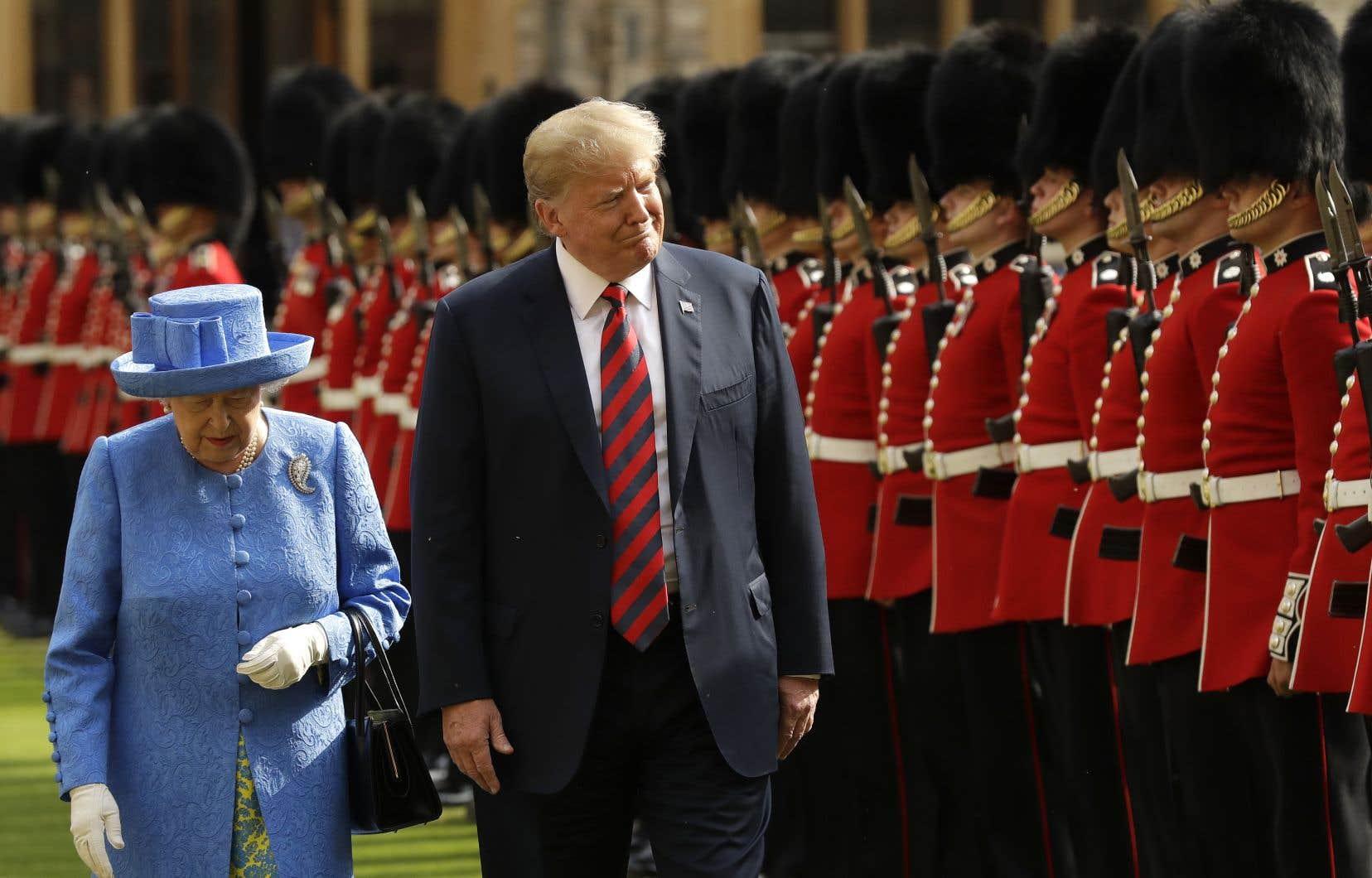 Elizabeth II a invité Donald Trump à passer en revue la garde d'honneur, des soldats vêtus du traditionnel uniforme rouge et coiffés du célèbre bonnet à poils d'ours.