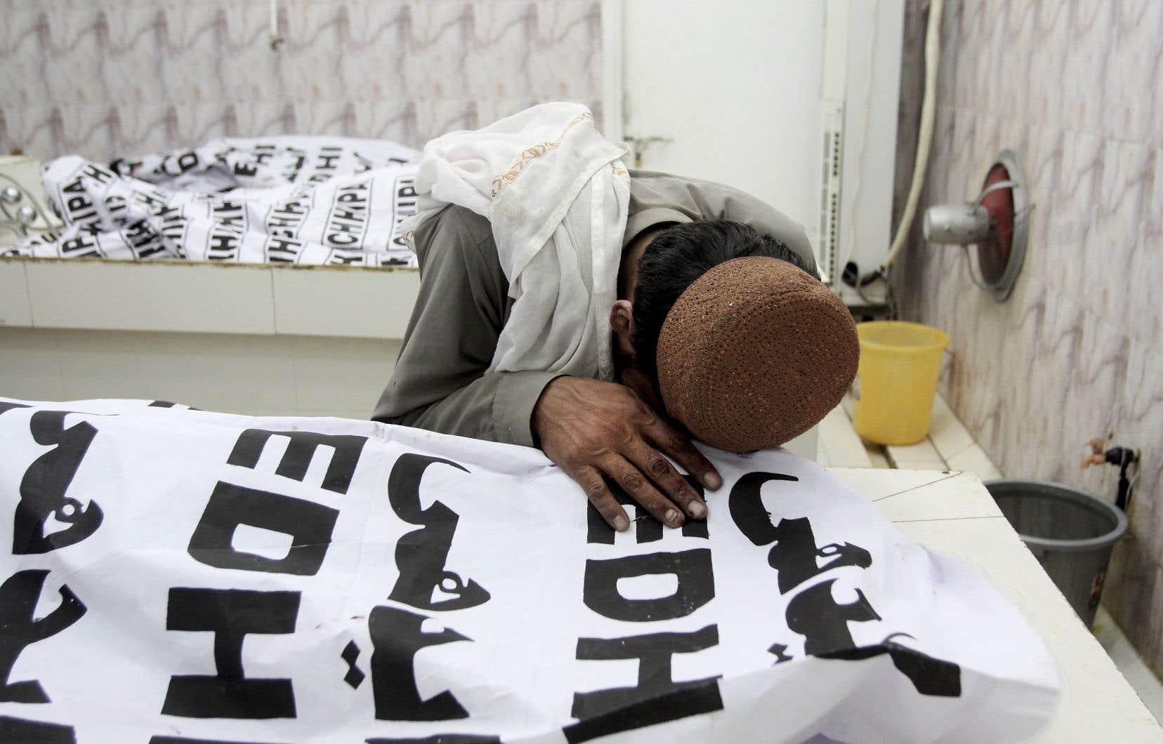 Un homme pleure sur le corps d'un membre de sa famille tué dans un attentat-suicide, dans une morgue de Quetta.