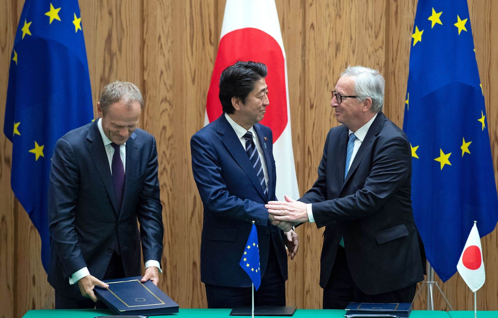 Le premier ministre japonais, Shinzo Abe, serre la main du président de la Commission européenne, Jean-Claude Juncker, en compagnie du président du Conseil européen, Donald Tusk, lors de l'annonce, mardi, de l'accord de libre-échange entre l'Europe et le Japon.