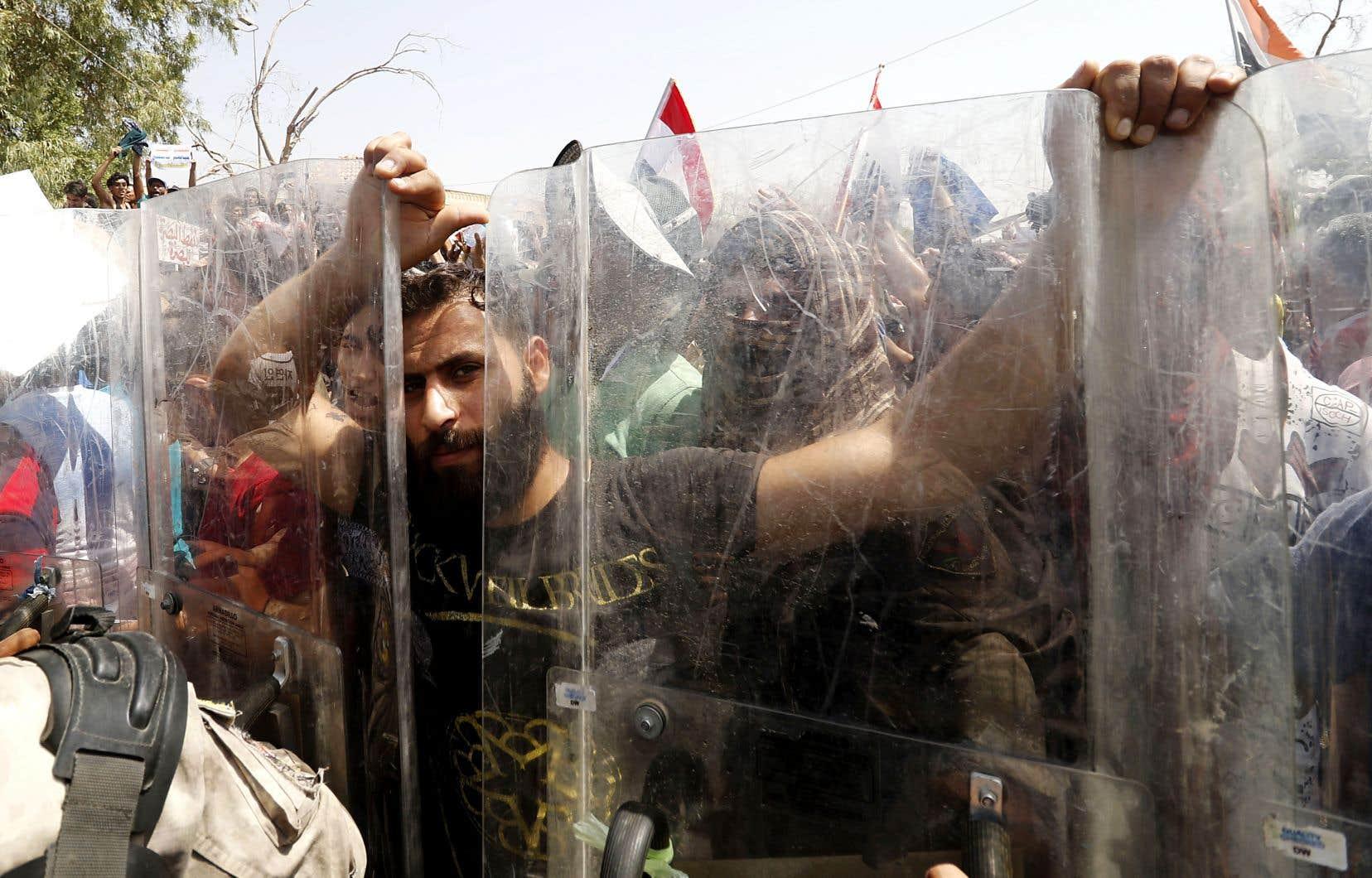 Un Irakien empoigne les boucliers policiers qui forment une barrière humaine, pendant une manifestation contre le gouvernement Al-Abadi, à Bassora, dans le sud de l'Irak, dimanche dernier.
