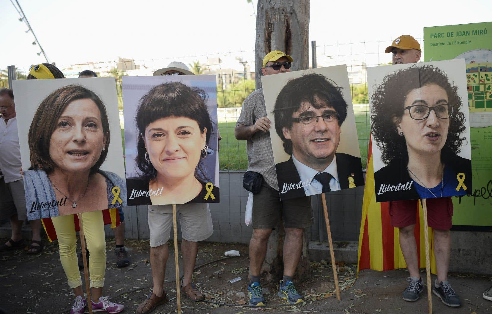Des personnes brandissent des photos de dirigeants catalans en prison ou en exil lors d'une manifestation de soutien aux dirigeants catalans emprisonnés le 14 juillet 2018 à Barcelone.