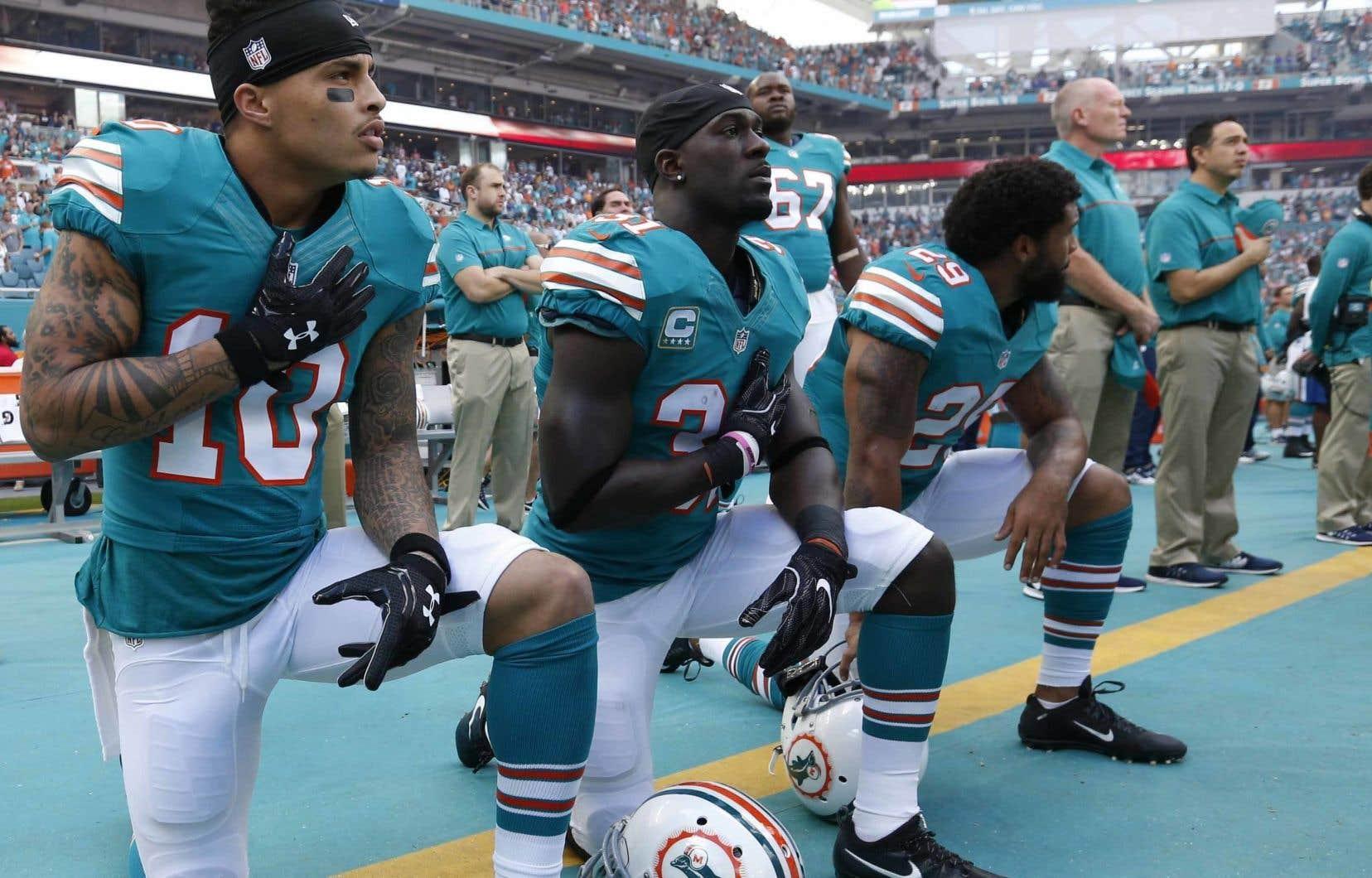 Les joueurs des Dolphins Kenny Stills, Michael Thomas et Chris Culliver s'agenouillent pendant l'hymne national, avant un match disputé en octobre 2016.