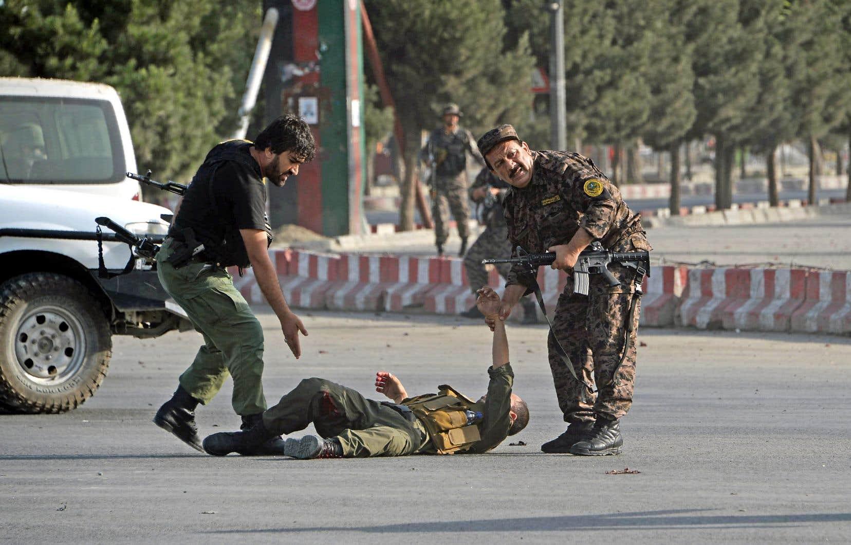 Des membres des forces de sécurité afghanes viennent en aide à un collègue blessé après l'explosion d'un kamikaze à Kaboul, dimanche.