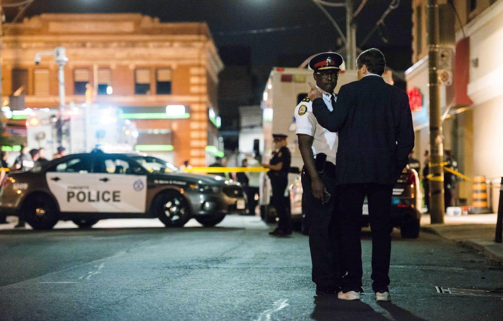 Le chef de la Police de Toronto, Mark Saunders, discute avec le maire John Tory, à proximité des lieux du crime.