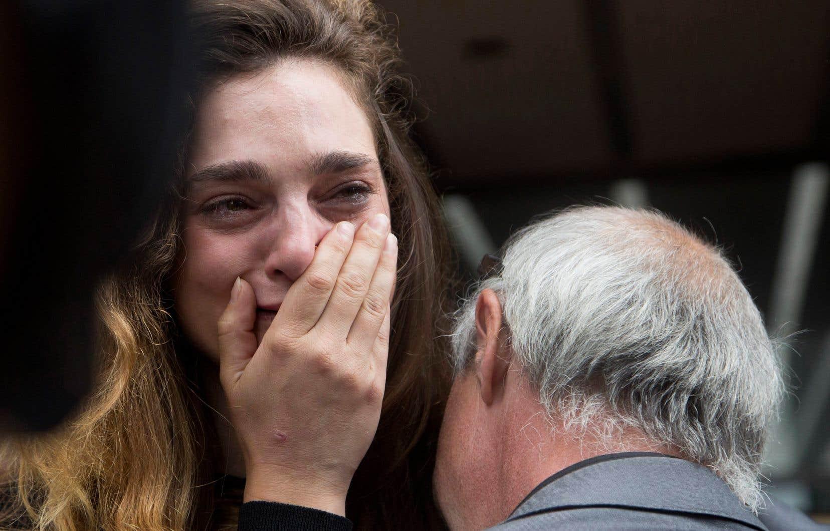 La journaliste Chelsia Rose Marcius n'a pu retenir ses larmes, alors que le photographe Todd Maisel tente de la consoler après leur licenciement, à l'extérieur des bureaux du quotidien, lundi à New York.