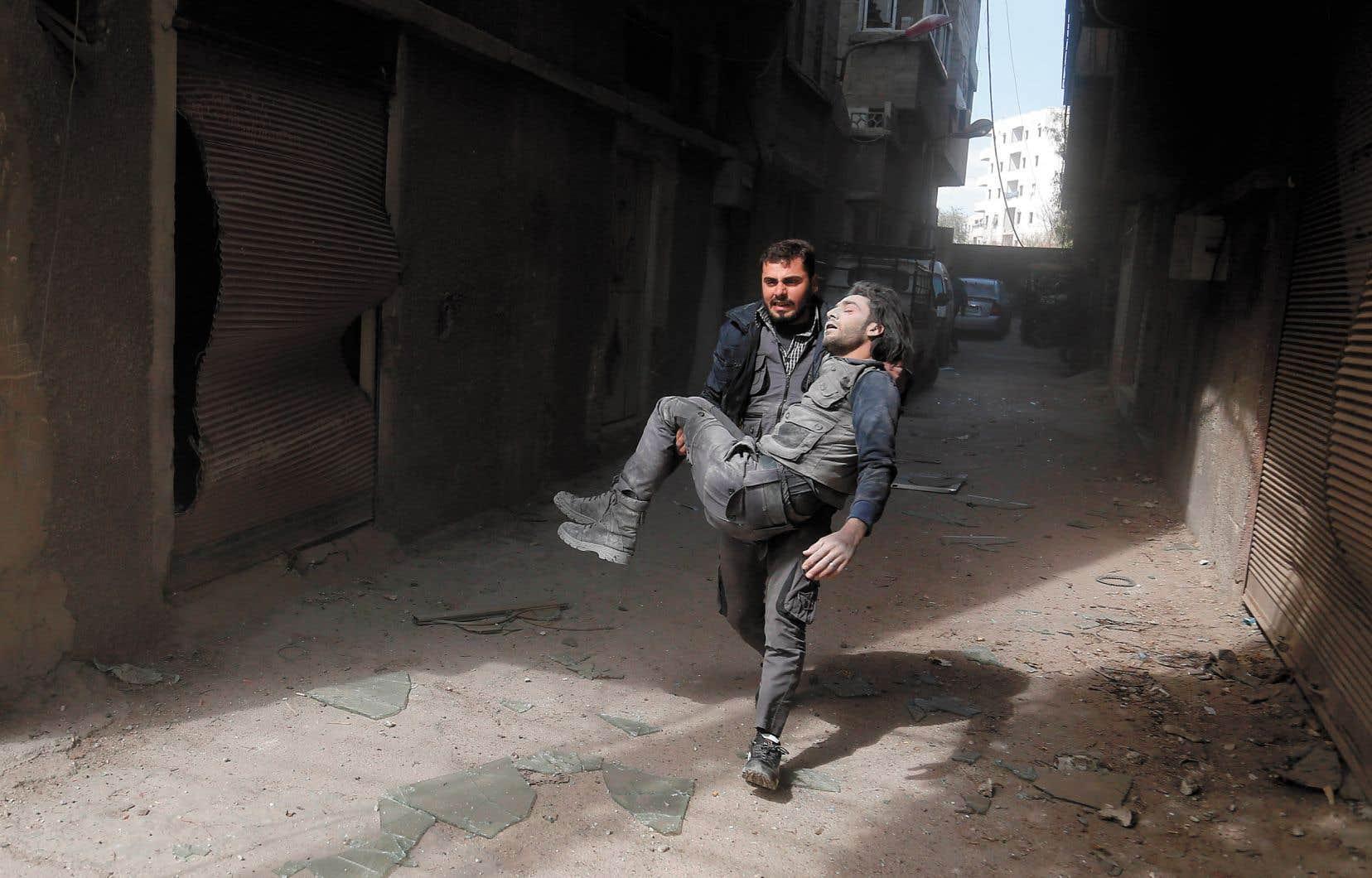Un Casque blanc évacue l'un de ses collègues après un bombardement dans la Ghouta orientale en mars 2017.