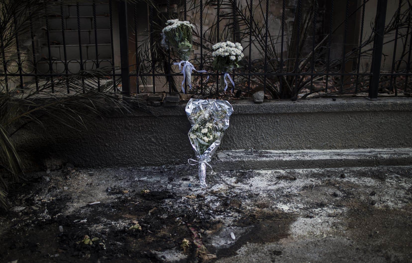 Des fleurs ont été déposées devant une résidence carbonisée de Mati où un couple a trouvé la mort.