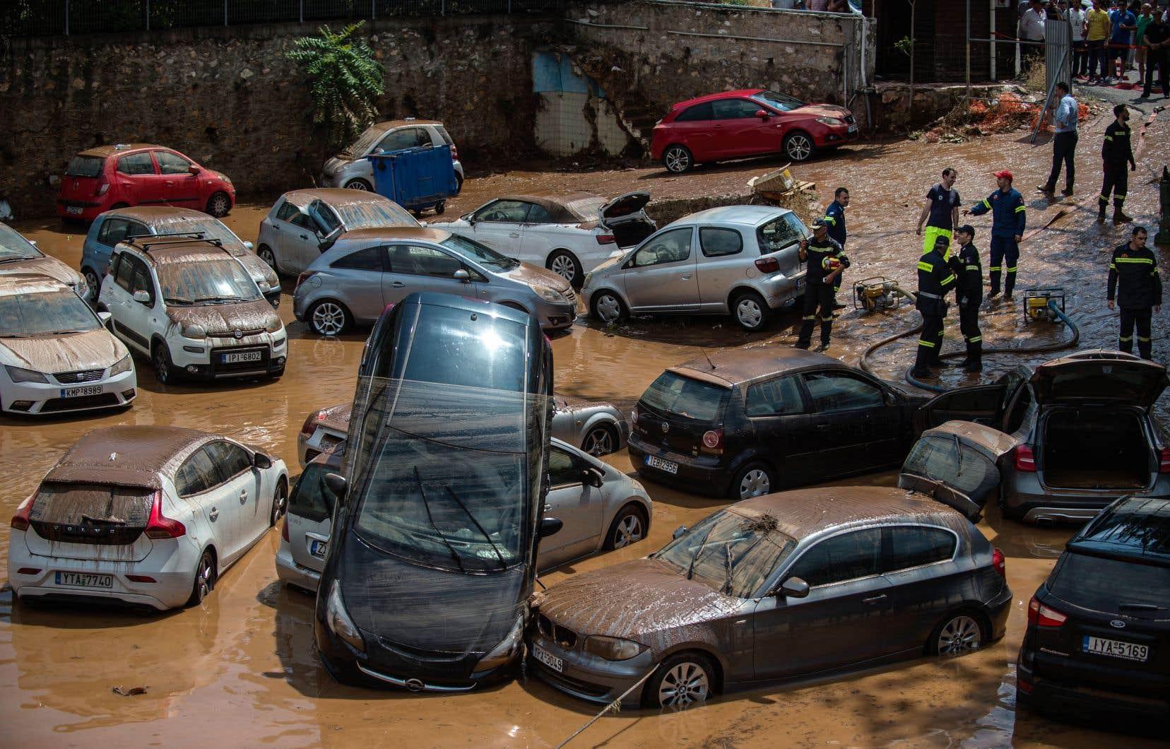 Des secouristes s'affairaient près de voitures qui ont été emportées par les flots à la suite d'inondations provoquées par de fortes pluies dans le nord d'Athènes.