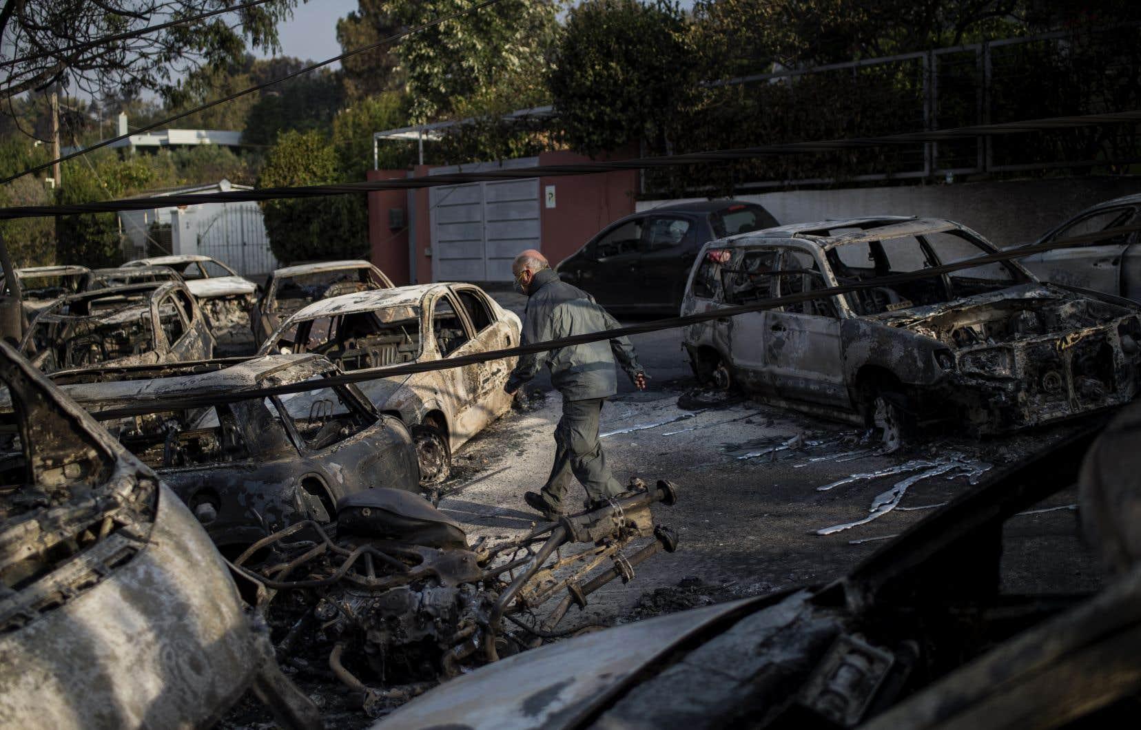 Une homme marche au milieu de voitures calcinées à Mati, la ville où se trouvaient la majorité des 82 morts.