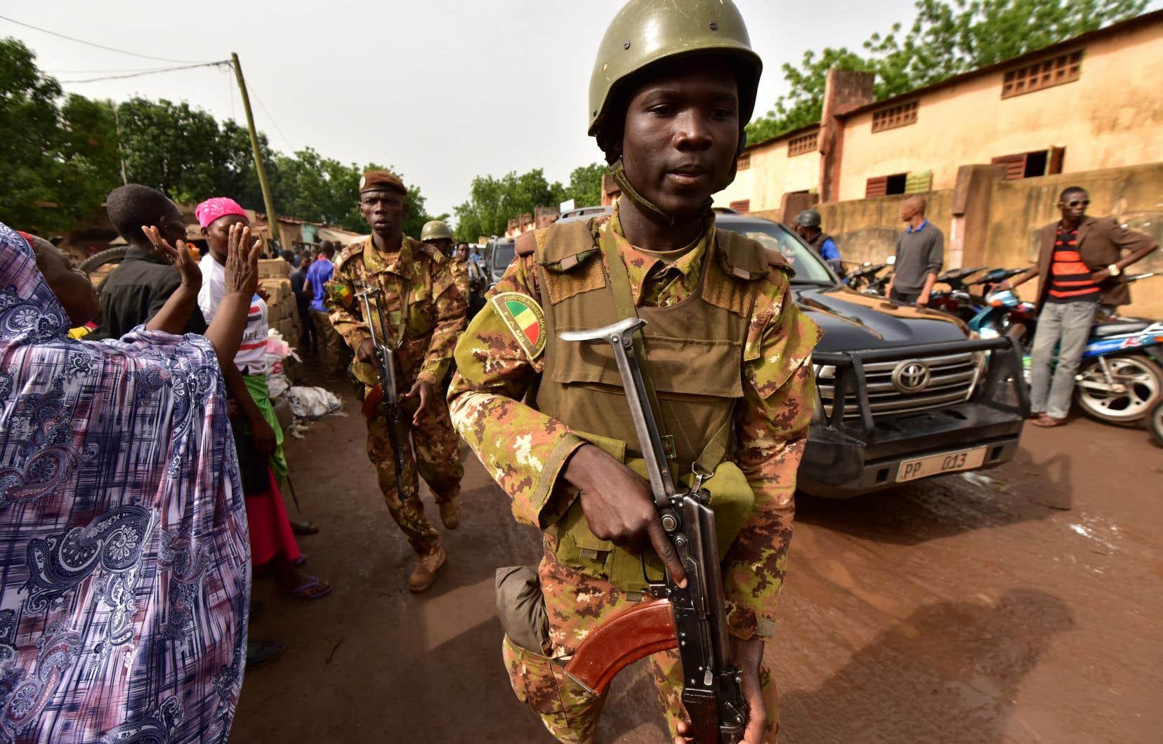 Des soldats escortent le président du Mali sortant, Ibrahim Boubacar Keïta, vers un bureau de vote à Bamako.