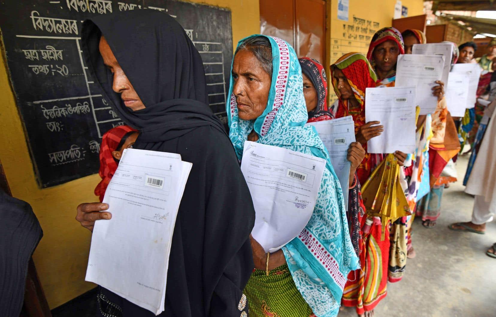 Des résidents de l'État d'Assam en Inde font la queue pour vérifier qu'ils figurent bien sur le registre national des citoyens, à Morigoan en Inde, le 30 juillet 2018.