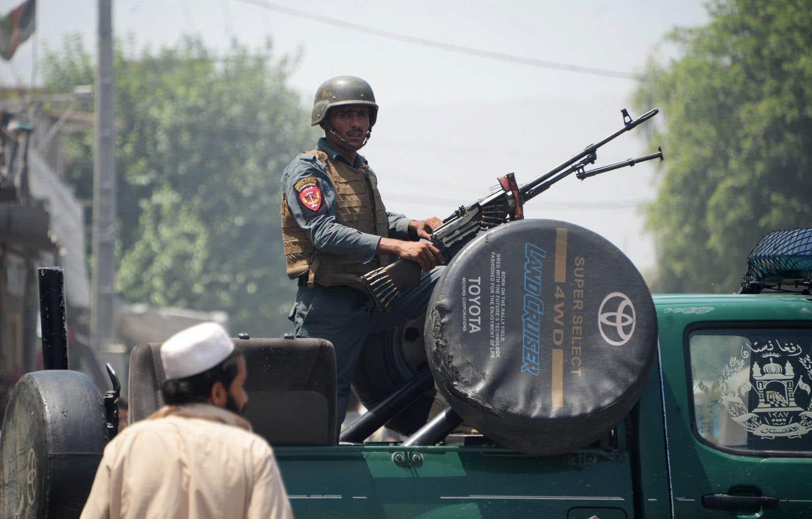 Un militaire afghan monte la garde au sommet d'un véhicule près du lieu de l'attentat suicide alors qu'une attaque est en cours entre les forces de sécurité afghanes et des kamikazes à Jalalabad le 31 juillet 2018.