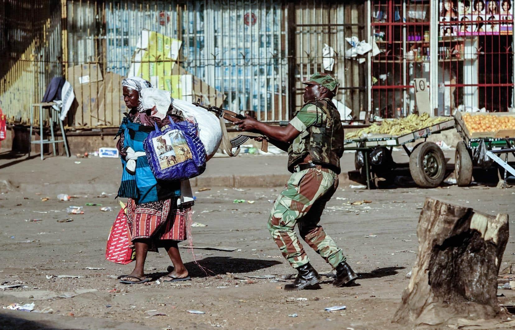 Une vendeuse a remballé ses marchandises alors qu'un militaire dispersait les manifestants, à Hararé.