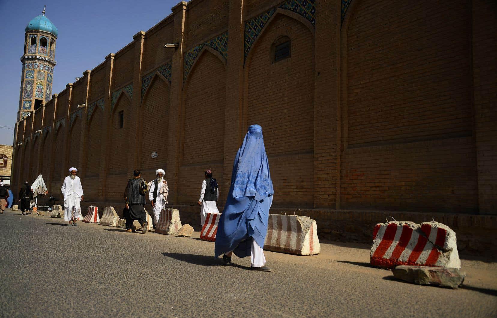 Une Afghane marche devant la mosquée Jama à Herat le 15 juillet 2018.