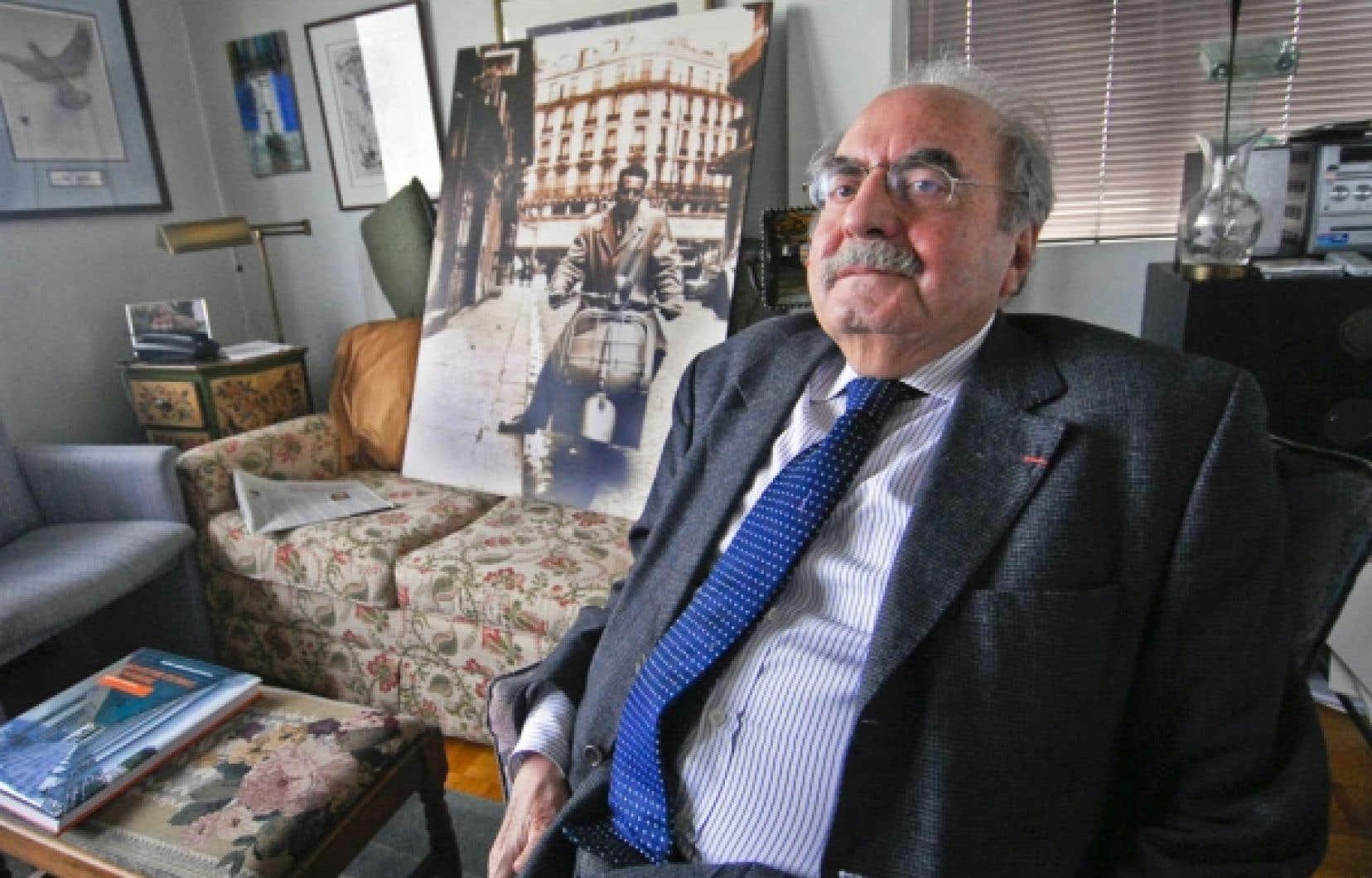 Naïm Kattan chez lui, devant une photo du temps où il se promenait en vespa à Paris.