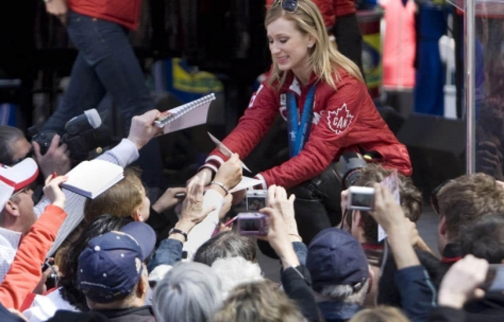 Une foule nombreuse a littéralement assailli la patineuse artistique Joannie Rochette, chaudement applaudie lors du défilé d'hier.