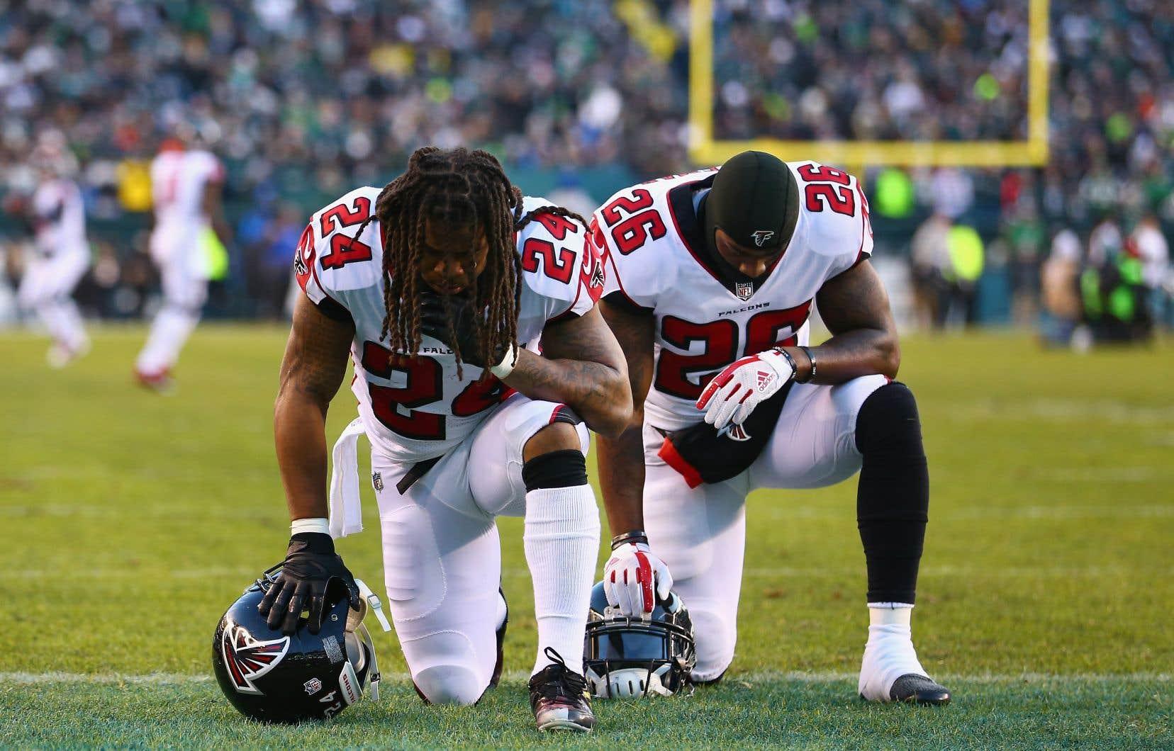 Des joueurs de la NFL mettent un genou à terre pendant l'hymne national pour dénoncer les violences policières et les tensions raciales aux États-Unis.