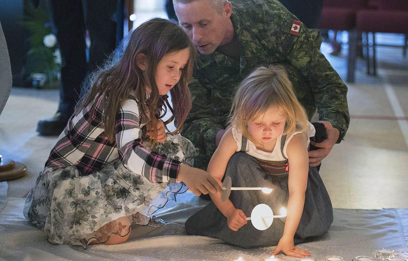 Un militaire de Fredericton et ses deux enfants ont allumé des lampions à l'église évangéliste de Fredericton en hommage aux victimes de la fusillade perpétrée vendredi.